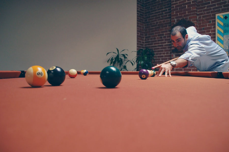 Man playing billiards near plants